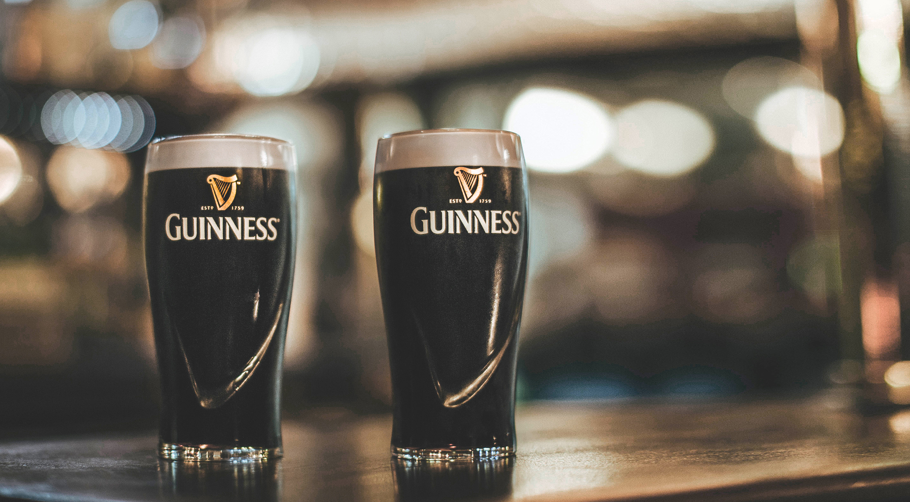 Two pints of Guinness on a bar