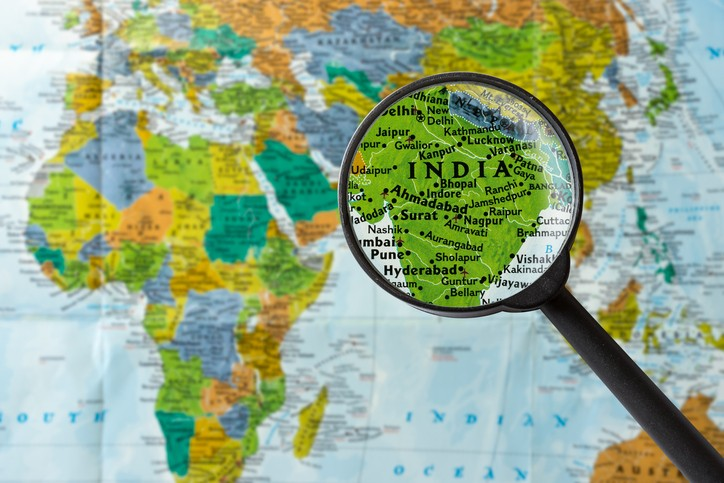 World map with magnifying glass zoomed in on India