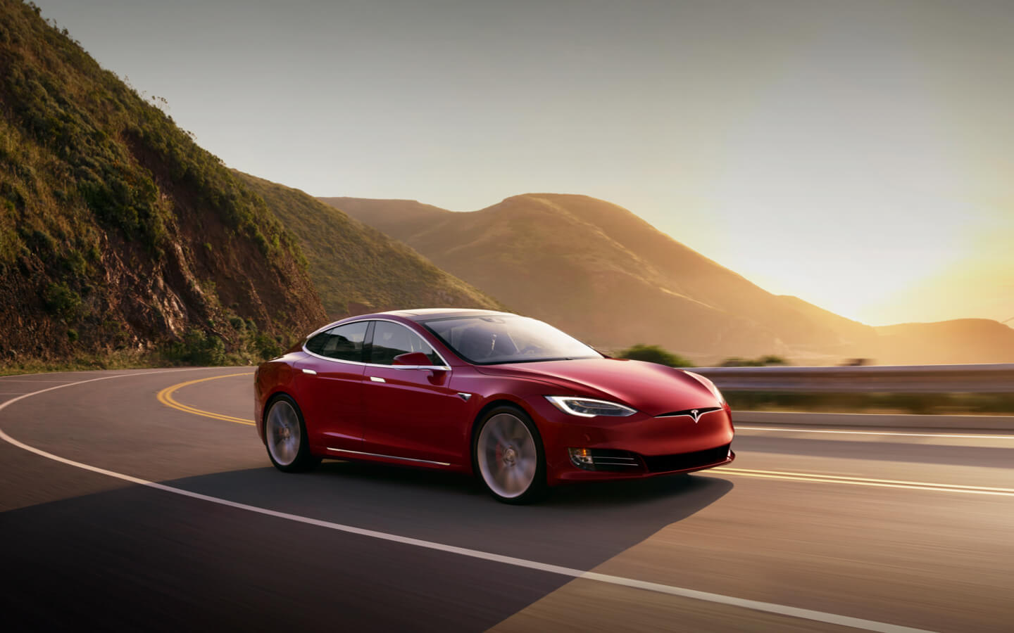 A red Model 3 Tesla electric car driving in the sunset